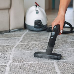 Woman cleaning the carpet with a steam cleaner